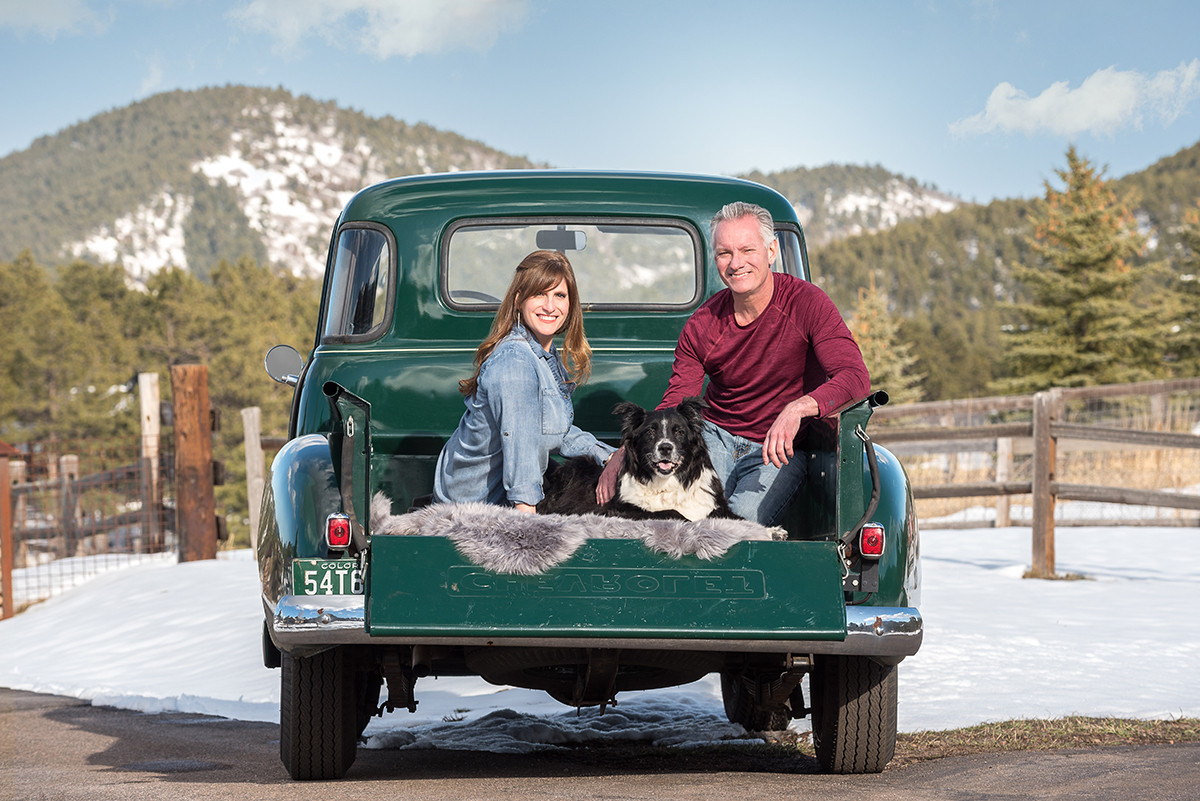 Couple posing with dog in back of 1952 Chevy truck