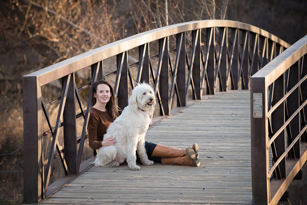 off-season dog photos featuring woman and Doodle dog sitting on bridge